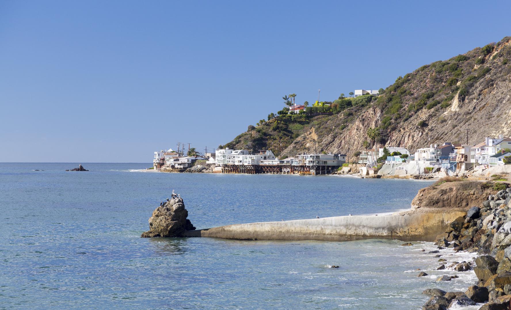 Modern houses overhang ocean and waves in Malibu California